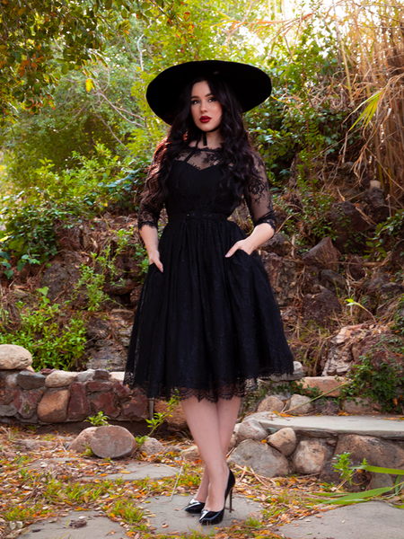 Positioned with her hands in her pockets and wearing a black sunhat, model Rachel Sedory looks ravishing in the Mourning Dress in Black Lace from La Femme en Noir.