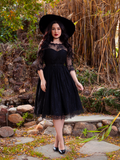 Slightly smiling model wears the gothic glamour inspired Mourning Dress in Black Lace from La Femme Noir.