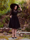 Rachel Sedory adjust the brim of her black sunhat while modeling the Mourning Dress in Black Lace from goth inspired clothier La Femme en Noir.