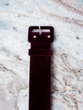 A product photo of the one and a half inch belt in oxblood velvet on a marble background.