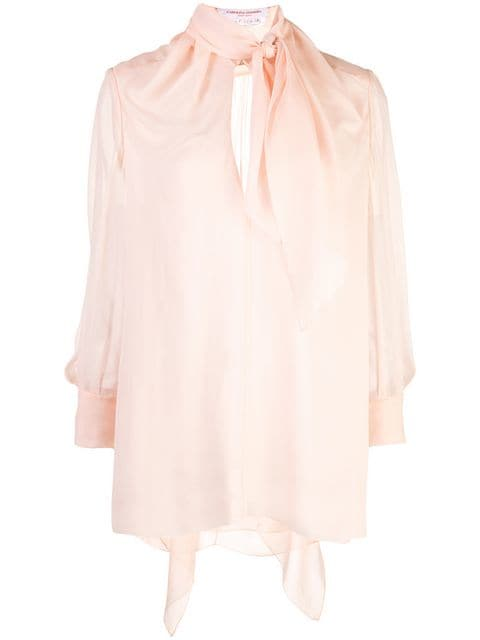 The CAROLINA HERRERA 3/4 Sleeve Blouse w/ Tie Neck is a shell pink silk pussy bow blouse featuring three-quarter length sleeves, button cuffs, a curved hem, a loose fit and a keyhole detail to the front.