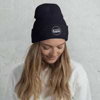 woman wearing a navy blue beanie hat with the AccessNow logo embroidered on it in the front, middle, in white thread