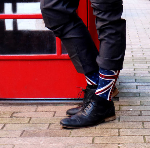 Model wearing Odd Union Jack Socks next to phone box