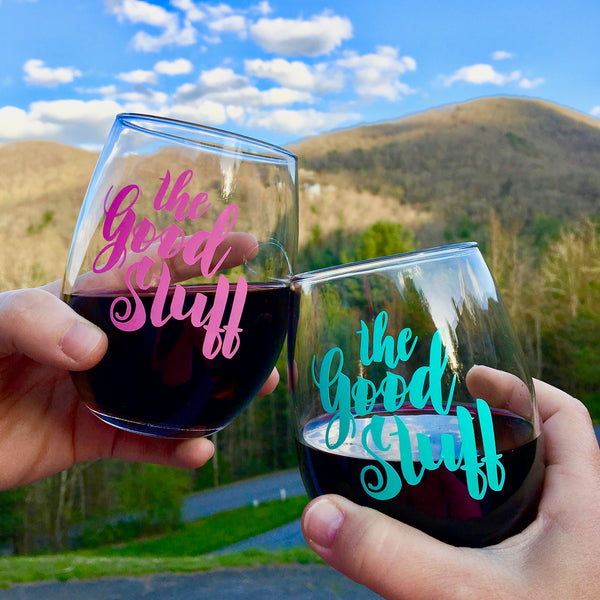 The Good Stuff stemless wine glass in front of the mountains and blue sky