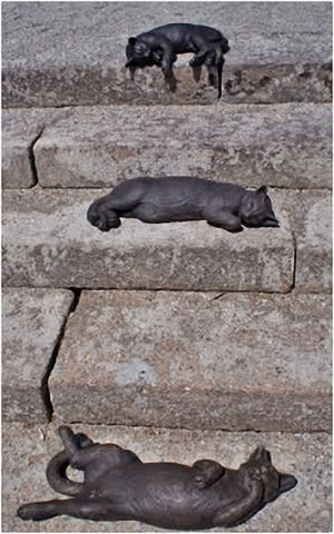 Sculptures of cats laying on stone steps