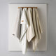 All Season blanket hanging on wall in white, natural, linen, and flint.