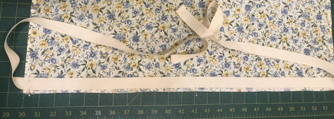 "Along the bottom edge on the right side of the fabric, align the bottom of a 1 ½ yard piece of twill tape with the top of the serging and align the center of the tape with the center of the fabric.  Sew the bottom edge of the twill tape down 1/8"" from the edge of the twill tape. Step 7"