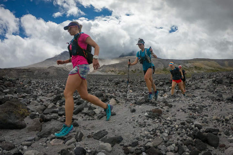 Shannon Payuer trail running with a group through mountainous terrain