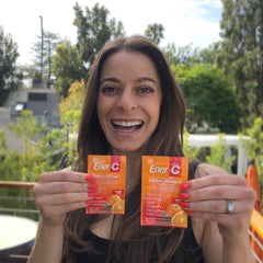 Jill Anenberg holding two packets of Ener-C's peach mango vitamin C drink mix