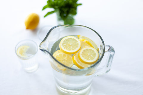 A water pitcher with cut up lemon slices for added vitamin C