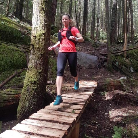 Trail running over a bridge in a forest while burning off excess energy and staying fit