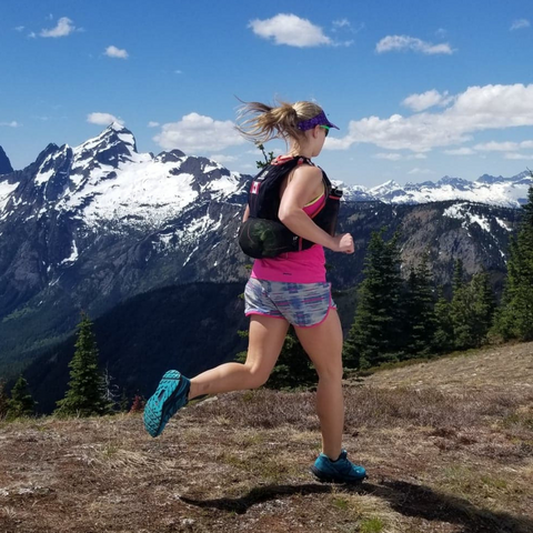 Girl cross country candidate running past majestic mountain