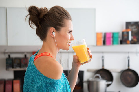 Woman drinking a healthy orange vitamin c drink to stay hydrated