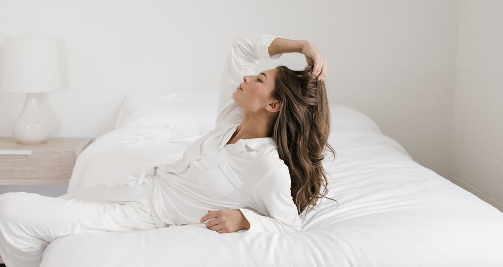 Woman touching her hair in Cozy Earth pajamas