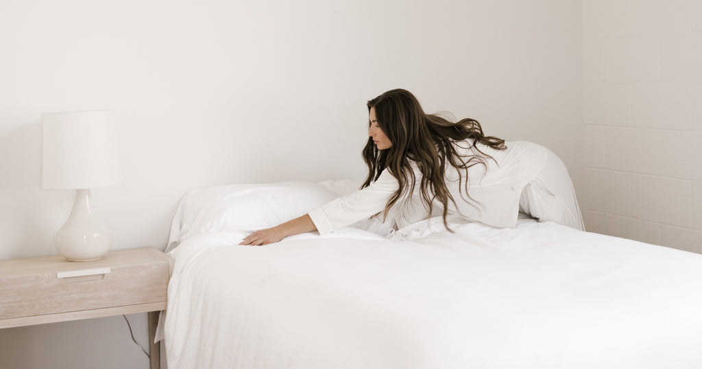 Woman making bed with Cozy Earth sheets