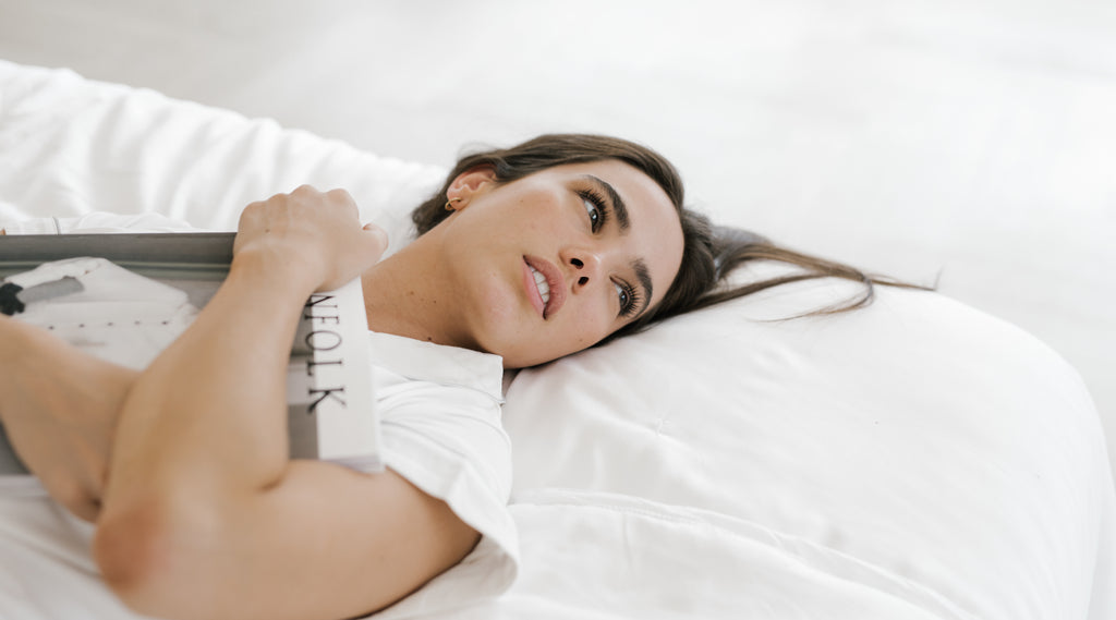 Woman with clear skin on Cozy Earth sheets