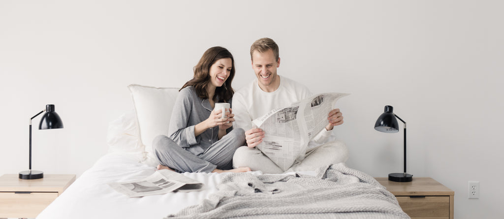 Husband and wife reading the newspaper in bed