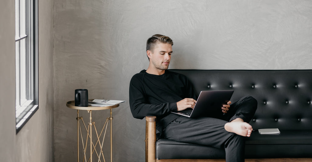 Man working in Cozy Earth loungewear on couch