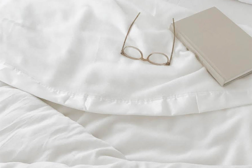 bamboo blanket spread over a bed with glasses and a book on top