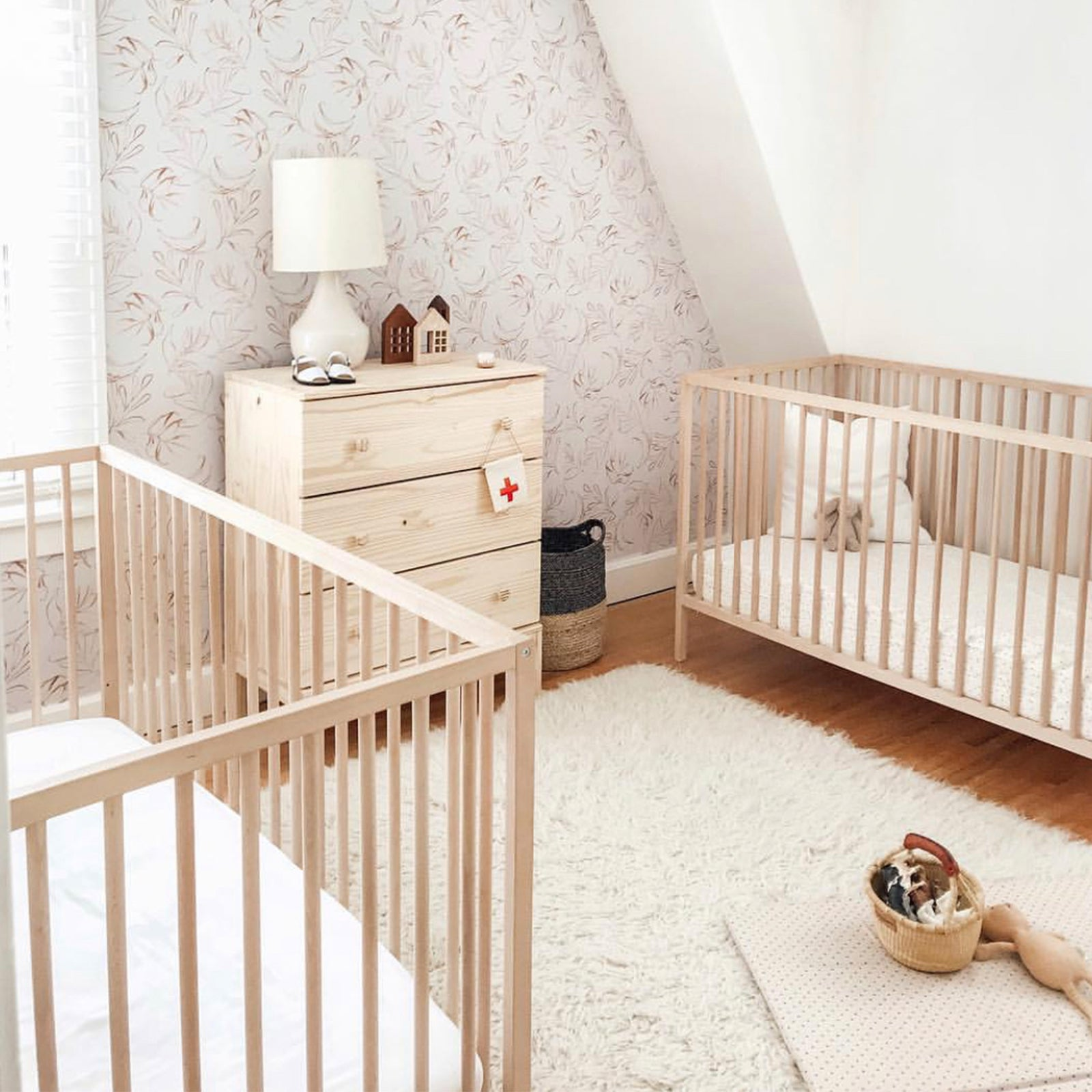 two wooden crib beds made with bamboo crib sheets in a nursery
