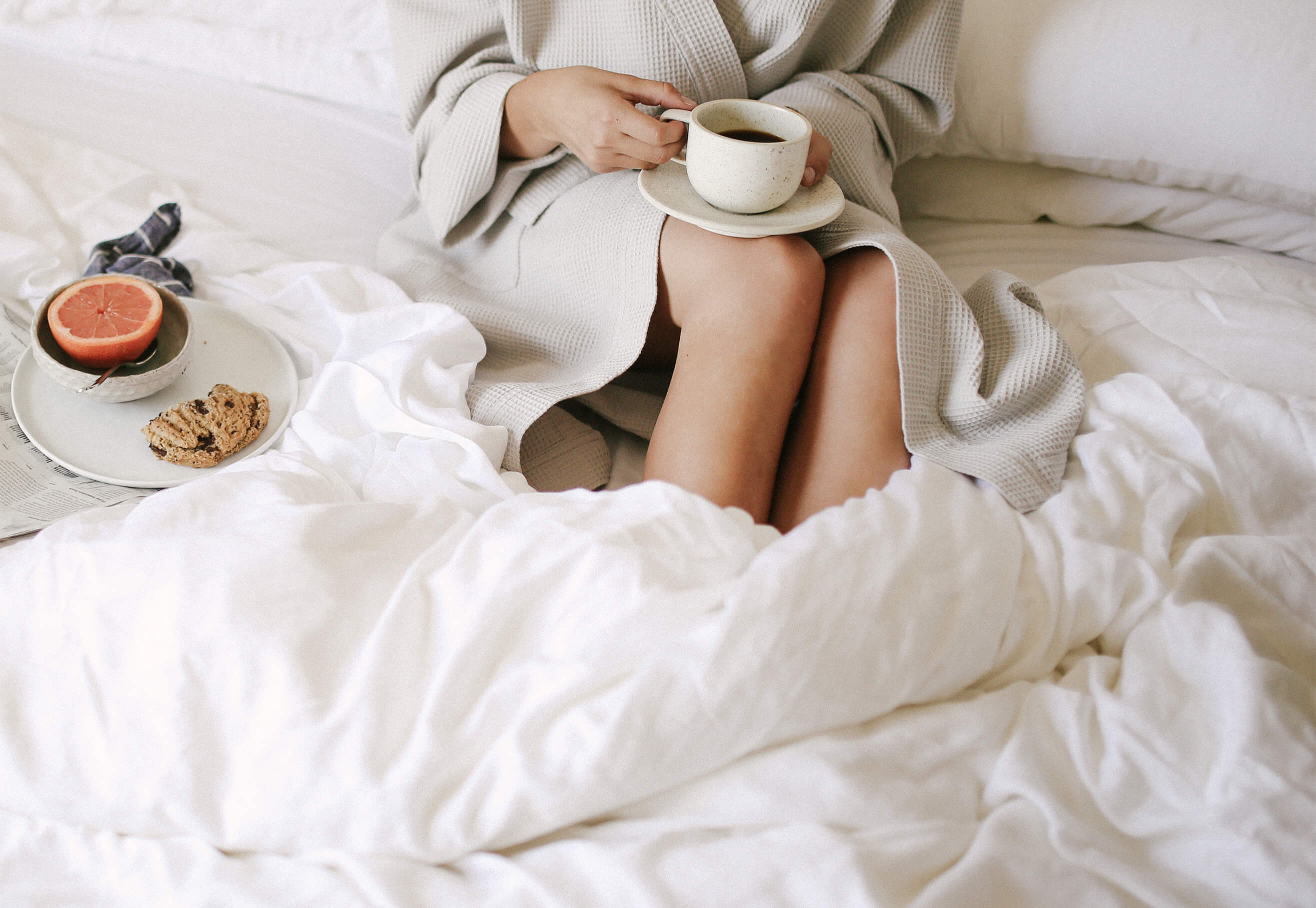 woman drinking coffee in bed warmed by her bamboo duvet cover