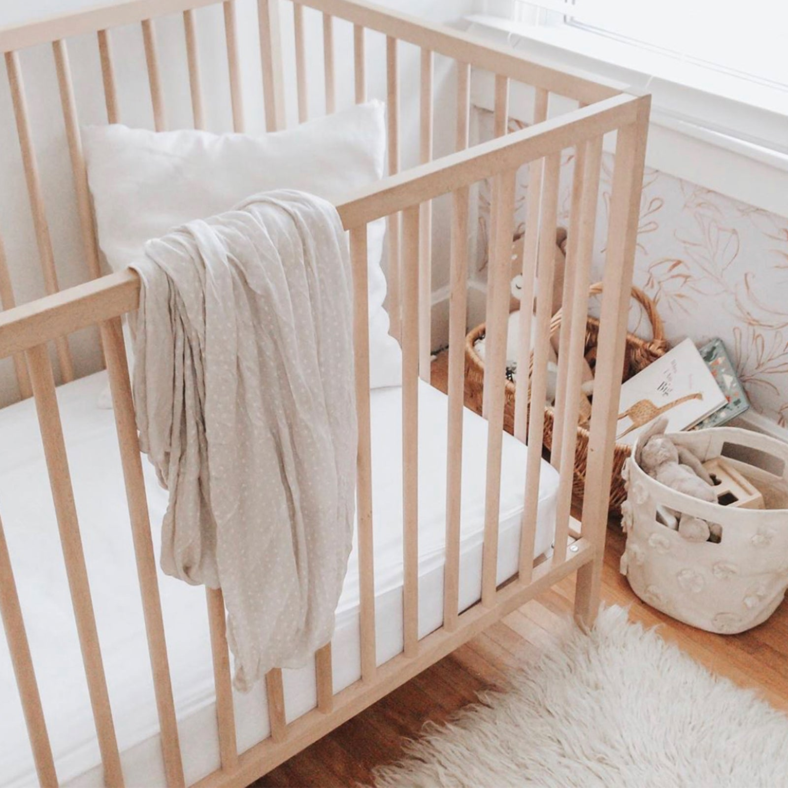 bamboo crib sheets draped over wooden crib