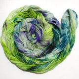 A bright swirl of yarn curls around itself like a labyrinth against a white background.