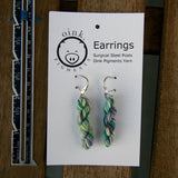 miniature skein earrings rest on a white card with the Oink Pigments logo and text at the top of the card.  a small ruler rests on the left.