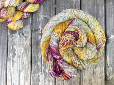 A bright swirl of yarn curls around itself like a labyrinth against a wooden background. Two skeins are peeking out of the upper left corner of the frame.