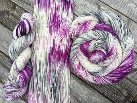 Three skeins, in three different arrangements (L to R: a doubled over twist, spread flat, and swirled around itself) rest against a grey wooden background.