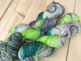 Two skeins of yarn rest diagonally in the frame against a wooden background. 4-Play colorway in disco base.
