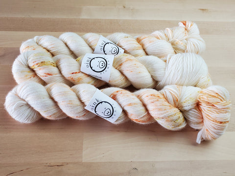 Three pale skeins of yarn with a light sprinkle of yellows and oranges, rest on a wooden background.