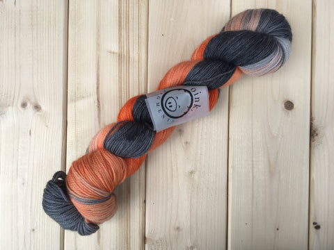 A twisted skein of orange and black-grey yarn lies against a light wooden background.