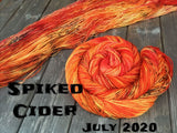 "skein of yarn twisted in a spiral and one laid out both are a bright orange with splashes of deep orange and black speckles, black text reads ""Spiked cider July 20202"""