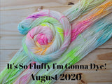 "yarn laid out with another skein twisted into a spiral, all skeins are colored a neon rainbow speckle, black text reads ""it's so fluffy I'm gonna dye! August 2020"""