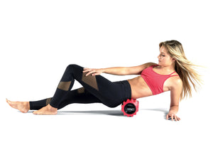 Red Phenom Vibrating foam roller being used on glutes and piriformis