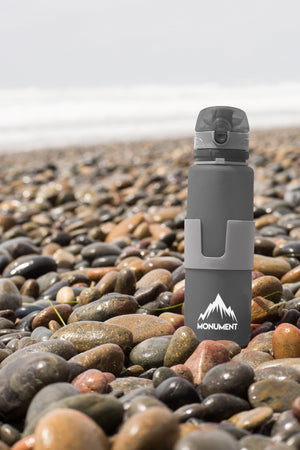 Grey Monument collapsible water bottle at beach in rocks