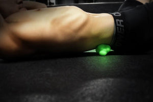 Green Trigger Point Self Massage tool being used on lower back