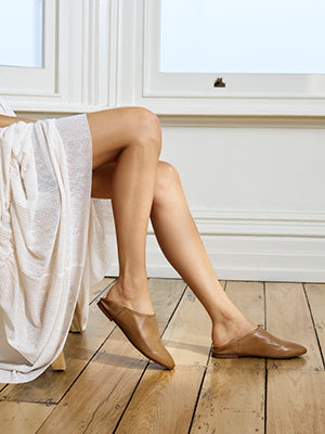 Woman modeling Larino flats in camel colour