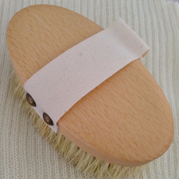Pet brush showing strap for hand
