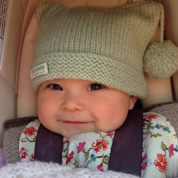 baby wearing mint merino pompom hat