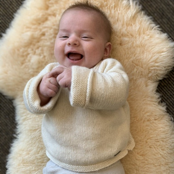baby wearing natural slouchy sweater laying on honey sheepskin rug