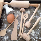 Children's wooden cooking set being used on kitchen bench