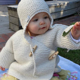 baby wearing natural merino double breasted jacket and chunky knit hat