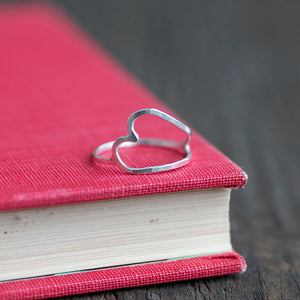 Understated and simple handmade heart ring on book jewelry display
