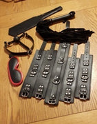 Black Faux leather bondage kit of collar, wrist & ankle cuffs, blindfold, ball gag, flogger & paddle