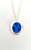 Oval pendant in abstract blue simple and stunning hand painted in bees wax and sealed in a glass cabochon