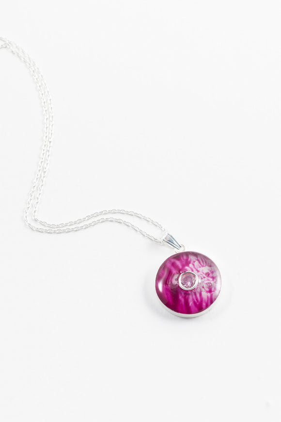 June birthstone beautifully placed on a cerise backdrop hand painted in wax and sealed in glass