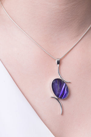 Model wearing Val B's Wax Sterling silver handcrafted pendant with purple cabochon hand-painted in wax  and sealed in glass