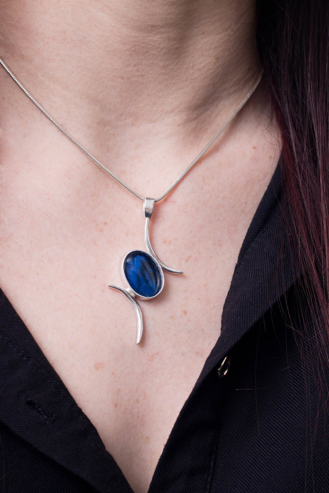 Model wearing Val B's Wax Sterling silver handcrafted pendant with blue cabochon hand-painted in wax  and sealed in glass